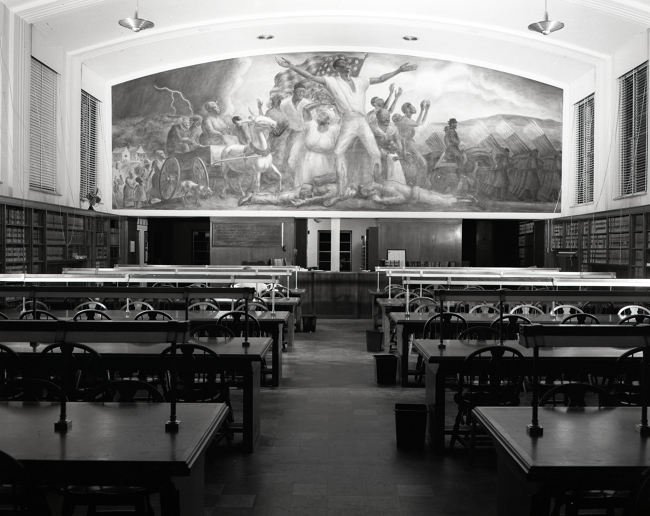 A black and white photograph of Curry's mural from the entrance to the room, with study tables in front of it and the circulation desk below