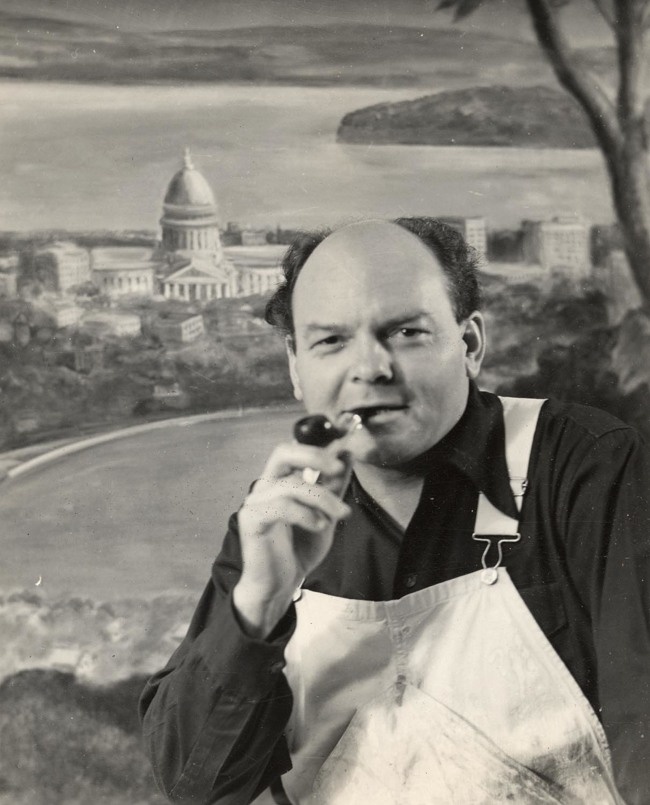 Archival photo of John Steuart Curry in painter's overalls in front of one of his paintings of Madison.