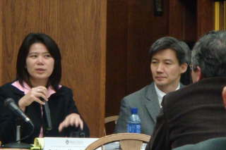 asian female and asian male seated conversing with individual who's back is to the camera