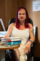 woman with long pink hair seated at a desk