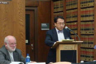 Asian male at podium, Caucasian male seated at left of podium