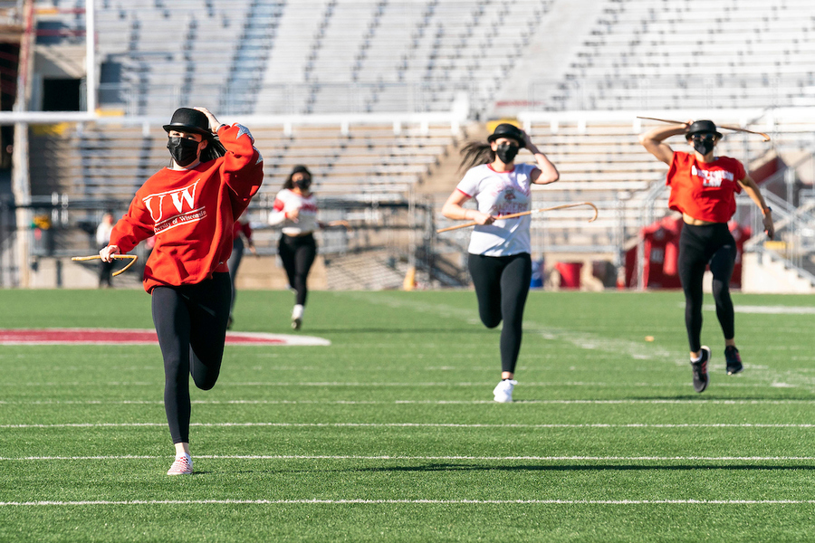students running on the field of Camp Randall for cane toss 2021