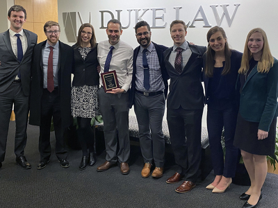 UW Law students and their coaches with their LawMeets competition trophy